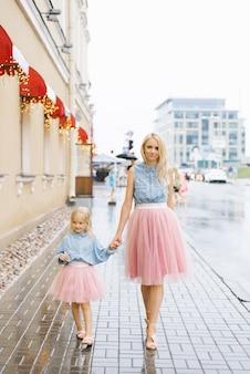 Mamma bionda e figlia piccola in gonne rosa e camicie di jeans. si tengono per mano e camminano sotto la pioggia in estate in città