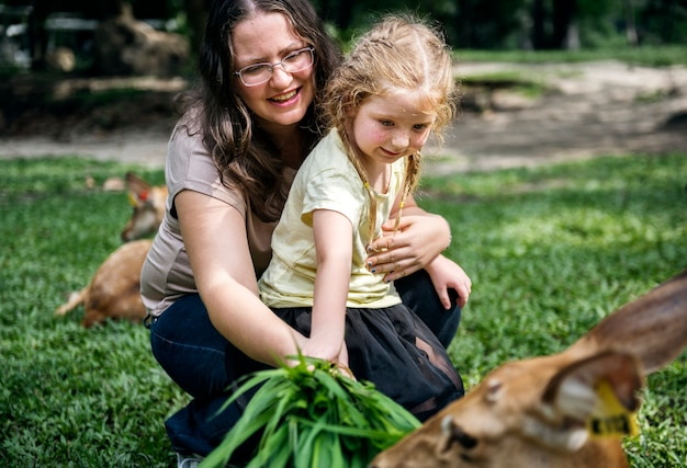 Mamma che aiuta il suo bambino ad alimentare i cervi
