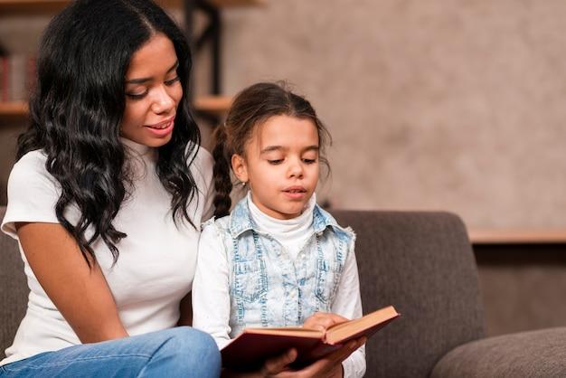 Mamma che ascolta sua figlia mentre legge
