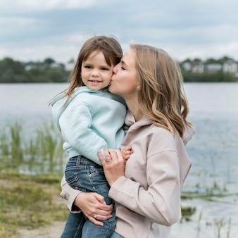 Mamma che bacia sua figlia vista frontale