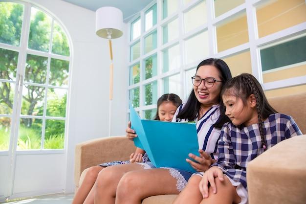 Mamma che insegna al libro di lettura di figlie sul sofà a casa