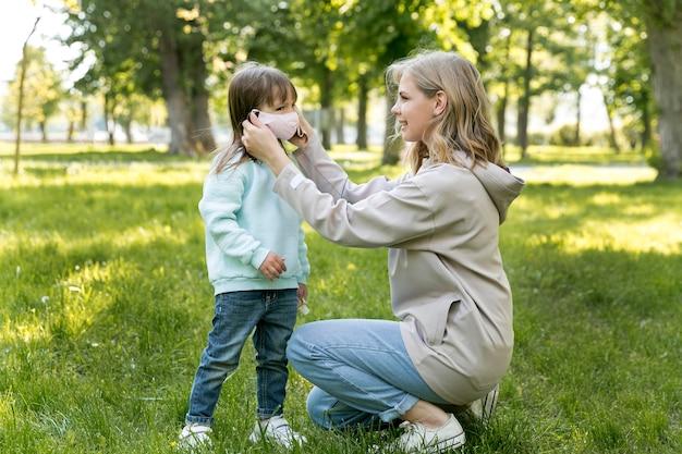 Mamma che mette la maschera medica di sua figlia