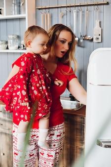 Mamma che tiene a mano piccola figlia, mostrando e guardando all'interno del frigorifero.