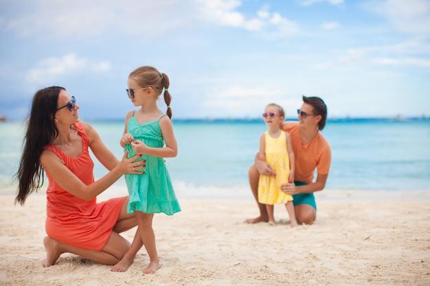 Mamma con sua figlia maggiore in primo piano e papà con la figlia più giovane in background sulla spiaggia