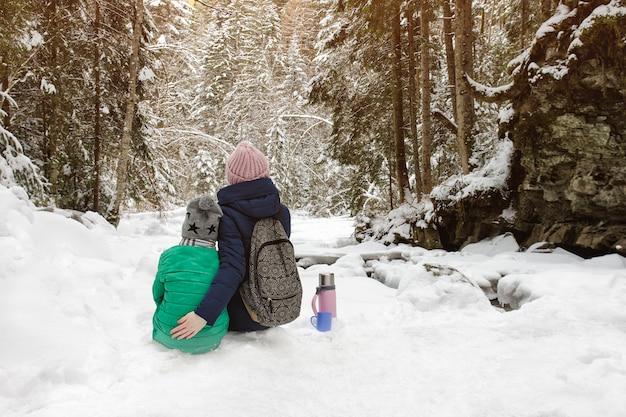 Mamma con suo figlio seduto e abbracciando nella foresta.
