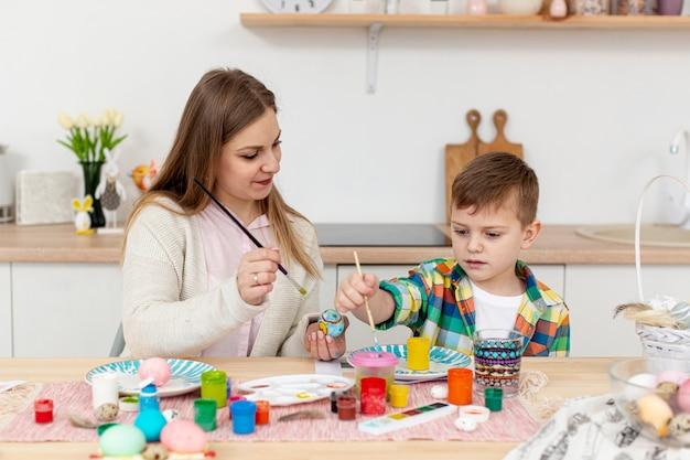 Mamma d'aiuto del figlio dell'angolo alto per dipingere le uova