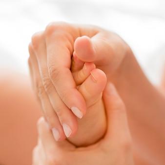 Mamma del primo piano che massaggia il piede del bambino
