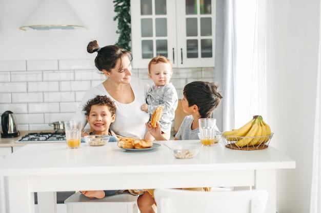 Mamma della giovane donna con la neonata sulle mani che cucina prima colazione sulla cucina luminosa a casa, grande famiglia felice