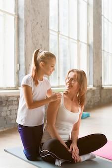 Mamma della tenuta della figlia che fa posa di yoga