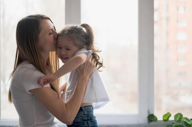 Mamma di vista laterale che abbraccia ragazza
