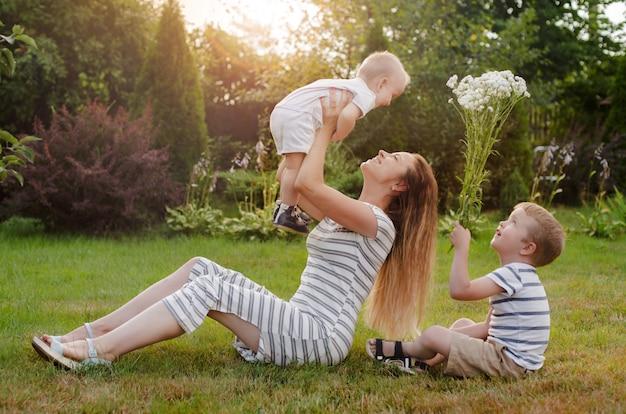 Mamma, due bambini riposano sulla natura. rivalità tra fratelli. fratelli, maternità.