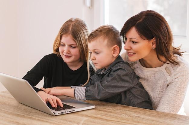 Mamma e bambini divertirsi sul portatile a casa