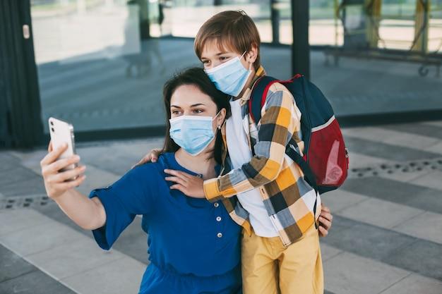 Mamma e bambino con uno zaino mascherato fanno un selfie al telefono prima di andare a scuola o all'asilo
