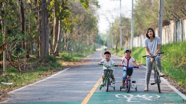 Mamma e due figli stanno andando in bicicletta sulla pista ciclabile.