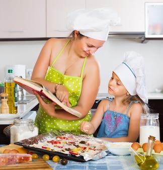 Mamma e figlia che decorano la pizza