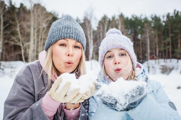 Mamma e figlia che giocano con la neve, soffiando neve dalle loro palme, passeggiata invernale