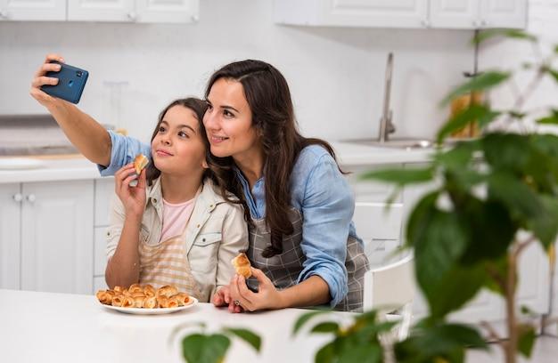 Mamma e figlia che prendono un selfie in cucina