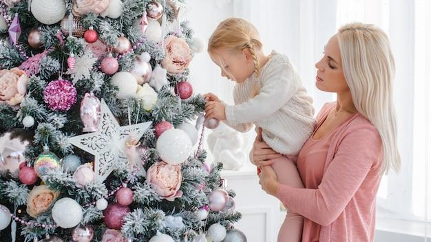 Mamma e figlia decorano l'albero di natale rosa al chiuso.