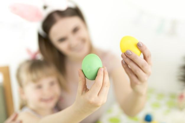 Mamma e figlia defocused con le uova dell'aster