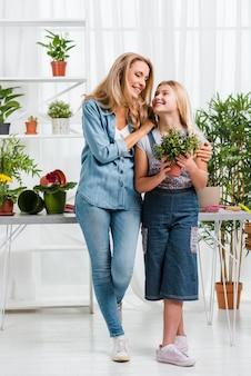 Mamma e figlia di smiley di angolo basso in serra