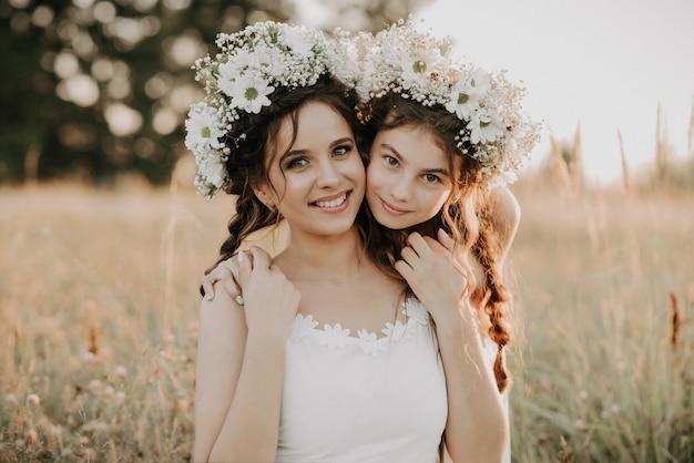 Mamma e figlia felici che sorridono e che abbracciano sull'erba nel campo di estate