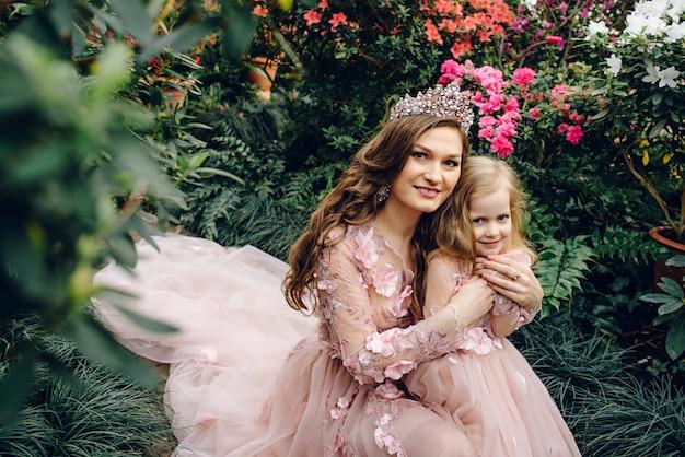 Mamma e figlia in lussuosi abiti color pesca in un giardino fiorito