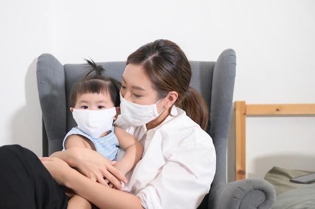 Mamma e figlia indossano una maschera protettiva a casa
