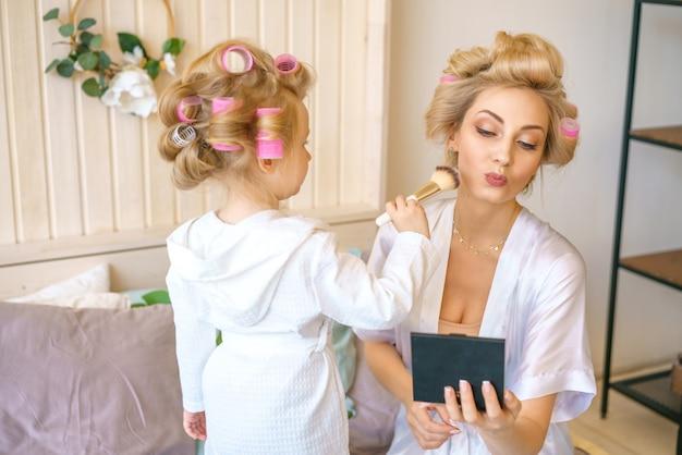 Mamma e figlia insieme felici in bigodini