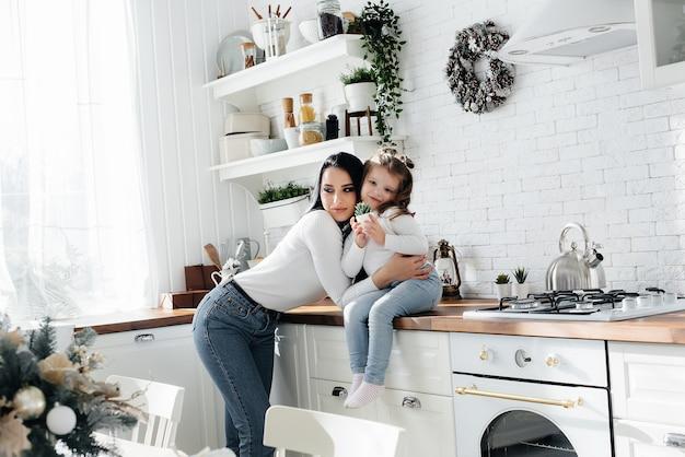 Mamma e figlia piccola cucinano in cucina e giocano. famiglia, felicità.
