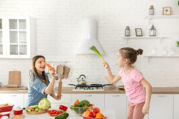 Mamma e figlia preparano un'insalata in cucina. divertiti e gioca con le verdure.