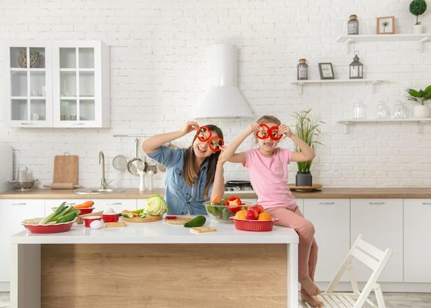 Mamma e figlia preparano un'insalata in cucina. divertiti e gioca con le verdure
