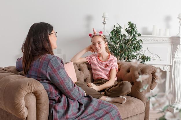 Mamma e figlia sono sedute sul divano e chiacchierano. l'adolescente con emozioni racconta a sua madre una storia. la figlia condivide i suoi sentimenti con il suo genitore. madri e figlie per il tempo libero