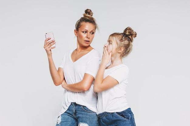 Mamma e figlia sorprese bionda in magliette e jeans bianchi facendo uso del concetto degli aggeggi dei telefoni cellulari isolato su fondo bianco