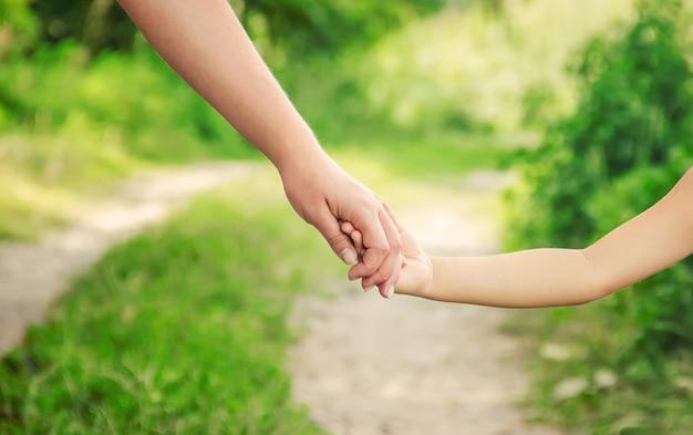 Mamma e figlia stanno camminando lungo la strada tenendosi per mano.