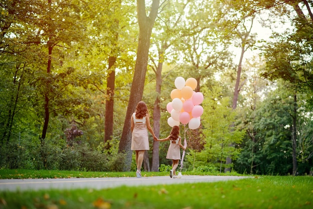Mamma e figlia, tenendosi per mano, camminano in estate nel parco con un grande mazzo di palloncini. l'amore della madre.