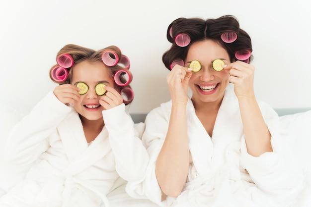 Mamma e figlia tengono in mano le fette di cetriolo.