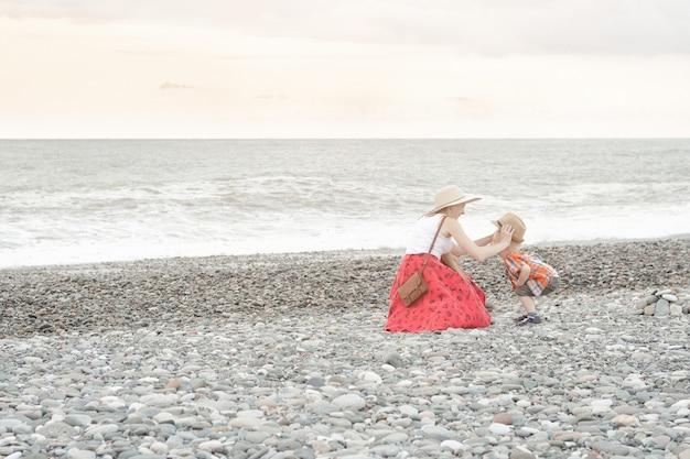 Mamma e figlio giocano sulla spiaggia. vista posteriore