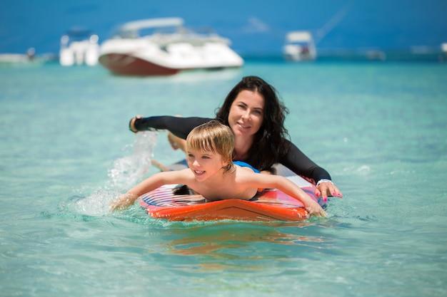 Mamma e figlio hanno surf nell'oceano sulla lavagna