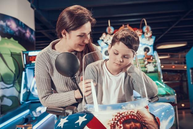 Mamma e figlio nel parco divertimenti sulla moto giocattolo nel centro.