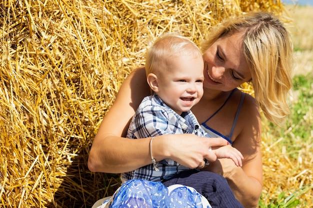 Mamma e figlio piccolo insieme sullo sfondo di un pagliaio in una luminosa giornata di sole