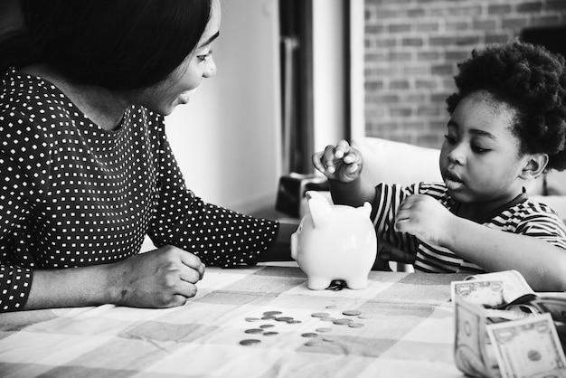 Mamma e figlio risparmiando denaro in un salvadanaio