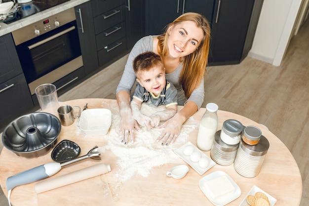 Mamma e figlio seduti dietro il tavolo della cucina con sopra cose da cucina. .