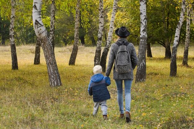 Mamma e figlio stanno camminando nella foresta d'autunno. vista da dietro