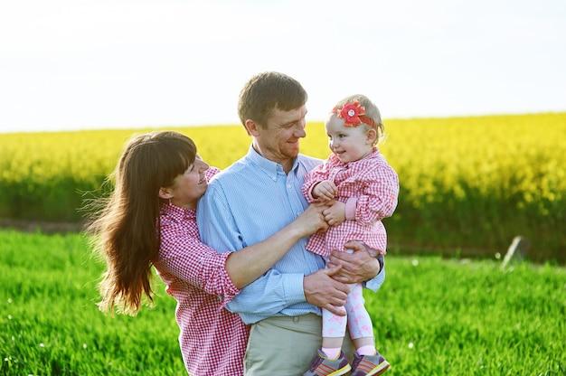 Mamma e papà e figlia stanno camminando sul campo estivo verde