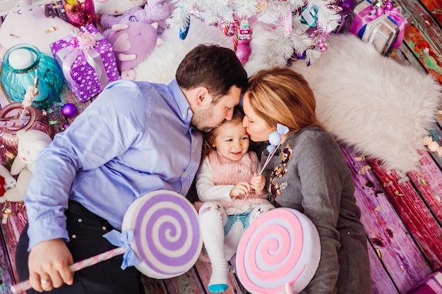 Mamma e papà tengono grandi caramelle rosa sdraiate con la figlia sul pavimento