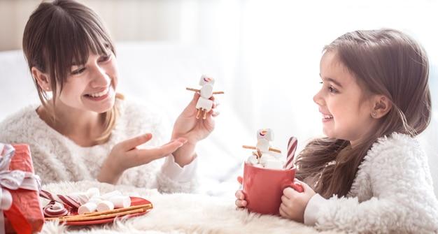 Mamma e piccola figlia sveglia che mangiano i dolci di natale