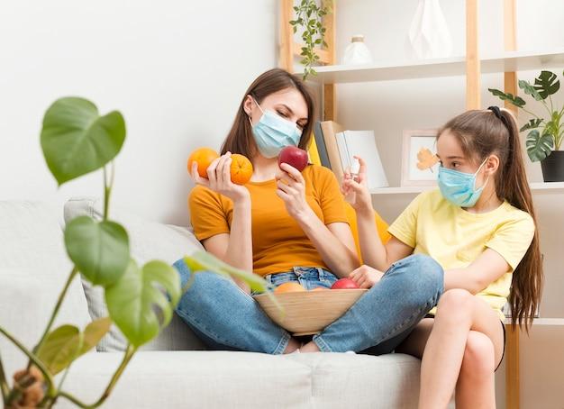 Mamma e ragazza che disinfettano i frutti prima del cibo