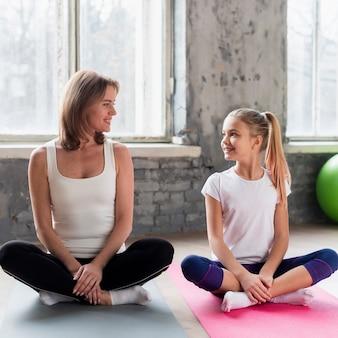 Mamma e ragazza che si siedono sulle stuoie di yoga che fanno posa guardando l'altro