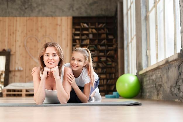 Mamma e ragazza in posa su stuoie di yoga