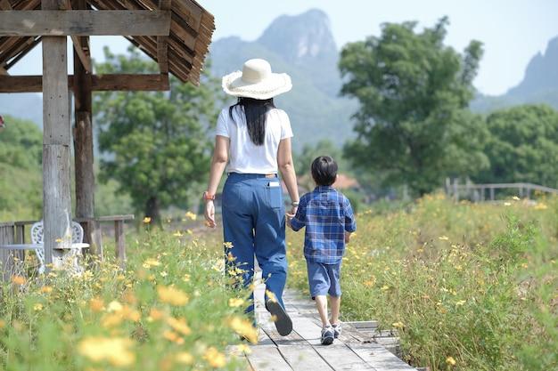 Mamma e sole che camminano in una natura